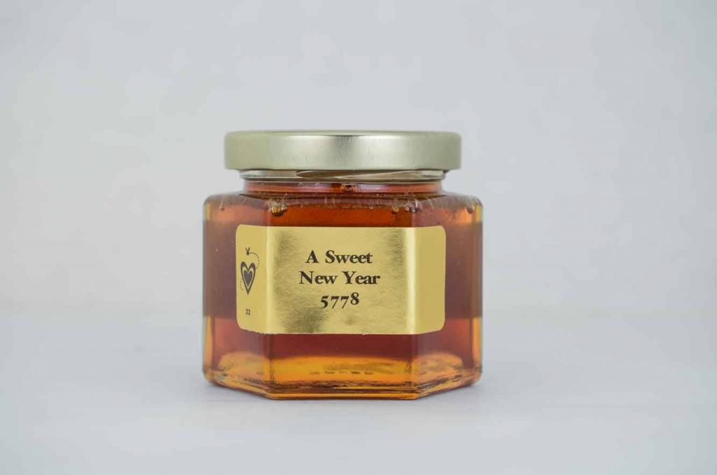 A Holiday 6oz. Honey Favor with gold foil label