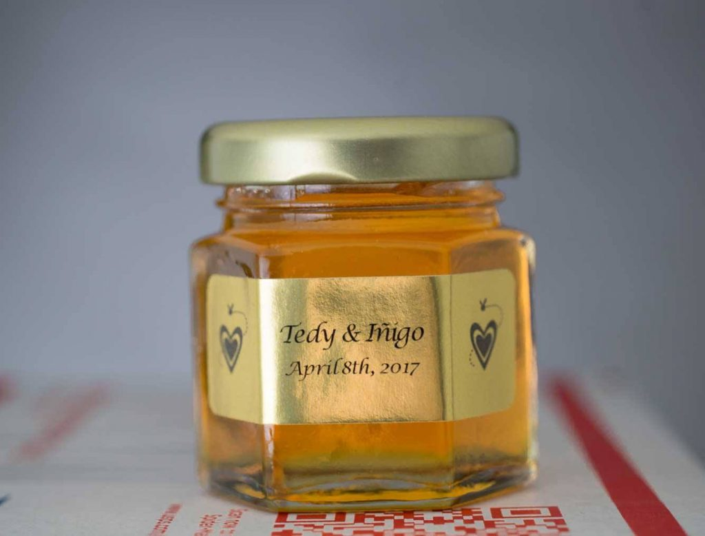 A 2oz. Wedding Honey Favor with personalized gold foil label